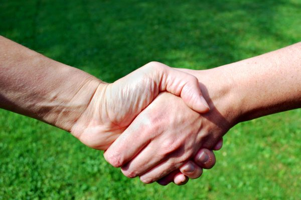 two people shaking hands in front of defocused green backgound